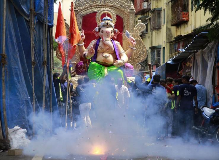 People light firecrackers near a huge idol of elephant headed Hindu god Ganesha during the Ganesh Chaturthi festival in Mumbai, India, Thursday, Sept. 17, 2015. The ten-day long festival celebrates Ganesha's birthday. (AP Photo/Rafiq Maqbool)