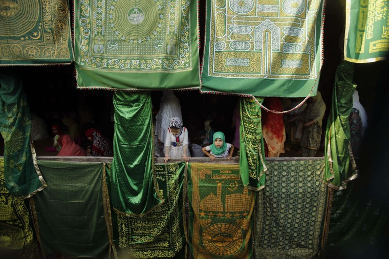Kashmiri Muslim children watch as others pray at the Shah-e Hamdan Mosque as they commemorate the death anniversary of sufi scholar Mir Syed Ali Hamdani in Srinagar, Indian controlled Kashmir, Wednesday, Sept. 16, 2015. Persian born Hamadani died in the year 1384 and was very influential in spreading Islam in Kashmir. (AP Photo/Mukhtar Khan)
