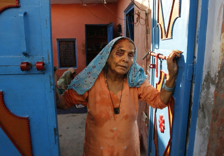 A bruised Asgari Begum, mother of 52-year-old Muslim farmer Mohammad Akhlaq, stands by the entrance of her home in Bisara, a village about 45 kilometers (25 miles) southeast of the Indian capital of New Delhi, Wednesday, Sept. 30, 2015. Indian police arrested eight people and were searching Wednesday for two more after villagers allegedly beat Akhlaq to death and severely injured his son upon hearing rumors that the family was eating beef, a taboo for many among Indiaís majority Hindu population. Since Prime Minister Narendra Modi, a Hindu nationalist, took office last year, hard-line Hindus have been demanding that India ban beef sales, a key industry for many within India's poor, minority Muslim community. In many Indian states, the slaughtering of cows and selling of beef are either restricted or banned. (AP Photo/Manish Swarup)