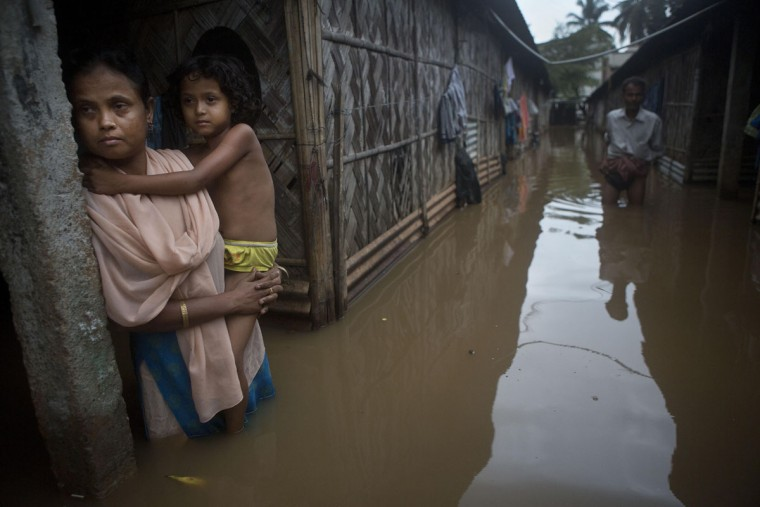 A woman holds her daughter stands awaiting her husband who went to collect drinking water after flood waters enter their house following heavy monsoon rains in Gauhati, India , Wednesday, Sept. 23, 2015. India receives its monsoon rains from June to September. (AP Photo/Anupam Nath)