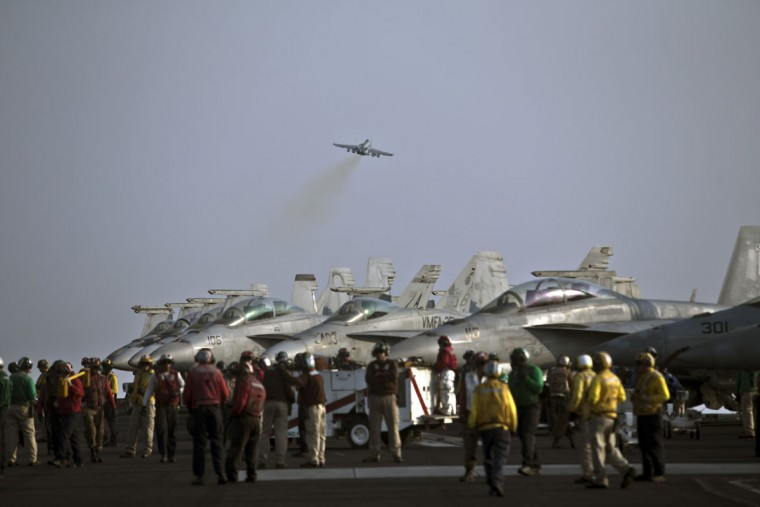 Flight deck personnel, wearing different colored shirts in order to distinguish their tasks, are seen on the deck of the USS Theodore Roosevelt aircraft carrier as a U.S. Navy fighter jet takes off. This island of steel in the Persian Gulf some 1,090-feet (330-meters) long is home to some 5,000 U.S. Navy airmen, sailors and Marine pilots, carrying some 70 aircraft involved in the fight against the extremists.(AP Photo/Marko Drobnjakovic)