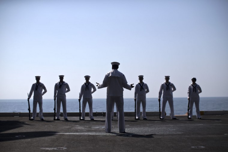 U.S. Navy sailors wear full dress white uniforms before a Sept. 11 remembrance ceremony on board the USS Theodore Roosevelt aircraft carrier deployed in the Persian Gulf in support of Operation Inherent Resolve, the military operation against Islamic State extremists in Syria and Iraq. (AP Photo/Marko Drobnjakovic)