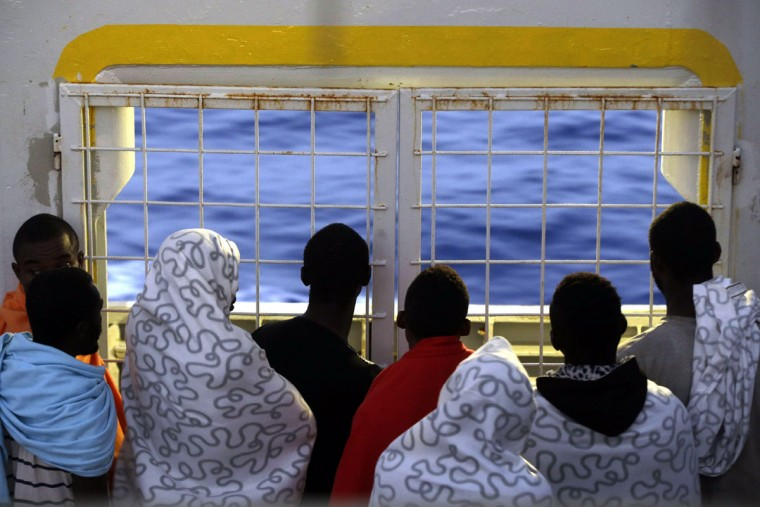 Migrants look at the sea as they crowd the bridge of the Norwegian Siem Pilot ship, Wednesday, Sept. 2, 2015. The Siem Pilot is carrying to the Italian Port of Cagliari hundreds of migrants rescued in several operations in the Mediterranean sea. (AP Photo/Gregorio Borgia)
