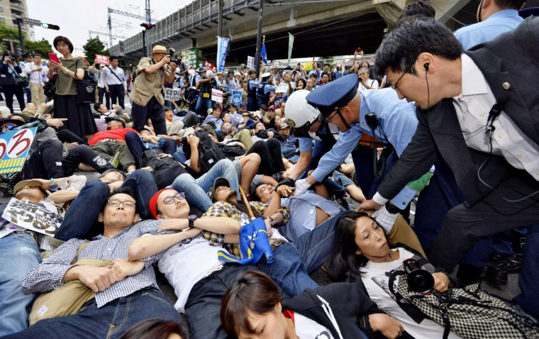 Protesters lie down arm in arm as police officers try to clear them in front of the venue hotel for a public hearing on the security legislation in Yokohama, south of Tokyo, Wednesday, Sept. 16, 2015. Opposition lawmakers and thousands of demonstrators were making last-ditch protests in a political showdown Wednesday as Japan's ruling party started a final push to pass security legislation to expand the role of the country's military. (Kyodo News via AP)