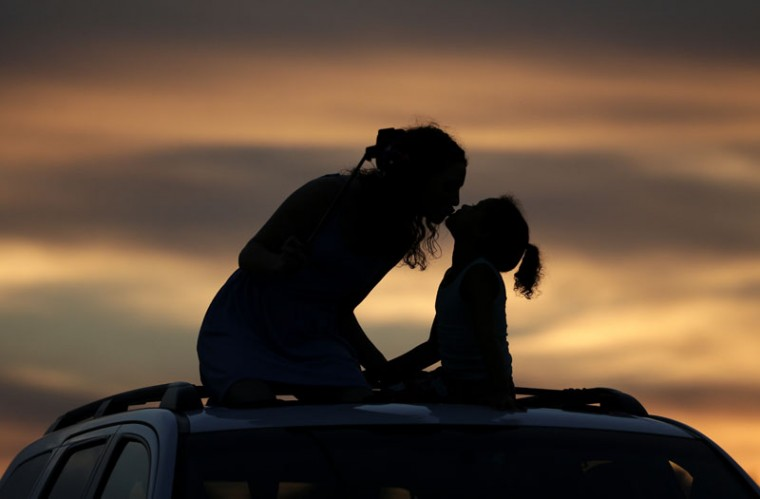 Savannah Anderson, left, kisses her sister Macy Saunders, 6, as they sit on top of a car to view a sunflower field at sunset, Saturday, Sept. 5, 2015, near Lawrence, Kan. The 40-acre field, planted annually by the Grinter family, draws hundreds during the weeklong late summer blossoming of the flowers. (AP Photo/Charlie Riedel)