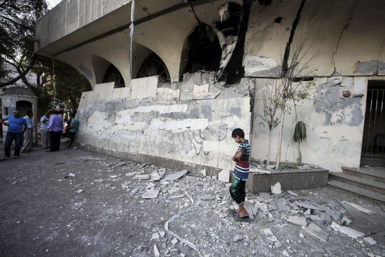 A boy walks around the site of an explosion as Egypt's security forces investigate the incident that damaged a nearby building with administrative offices for Egypt's Ministry of Foreign Affairs in Cairo, Egypt, Sunday, Sept. 20, 2015. Egypt's state news agency MENA said a few people were injured when a bomb exploded in a middle-class neighborhood of Cairo. (AP Photo/Mahmoud Abo El-Dahab)