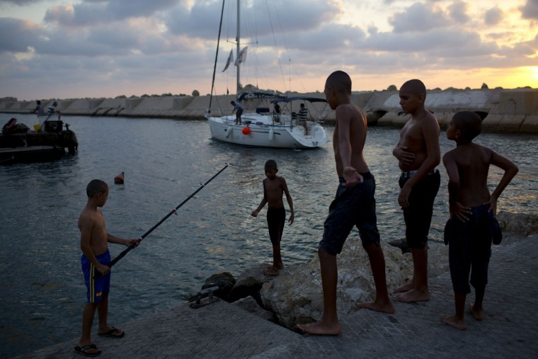 Israeli Arab youths play on a pier at the old port of Jaffa, a mixed Jewish-Arab part of Tel Aviv, Israel, Thursday, Sept. 3, 2015. (AP Photo/Oded Balilty)