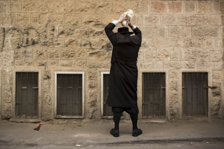 An ultra-Orthodox Jewish man swings a chicken over his head as part of the Kaparot ritual in Jerusalem, Sunday, Sept. 20, 2015. Observers believe the ritual transfers one's sins from the past year into the chicken, and is performed before the Day of Atonement, Yom Kippur, the holiest day in the Jewish year which starts at sundown Tuesday. (AP Photo/Oded Balilty)