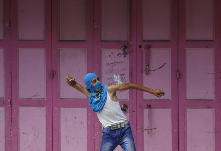 A Palestinian protester throws a stone during clashes with Israeli soldiers in the West Bank city of Hebron, Tuesday, Sept. 29, 2015. Palestinian demonstrators clashed with Israeli troops across the West Bank on Tuesday, as tensions remained high following days of violence at Jerusalem's most sensitive holy site, revered by Jews as the Temple Mount and by Muslims as the Noble Sanctuary. (AP Photo/Nasser Shiyoukhi)