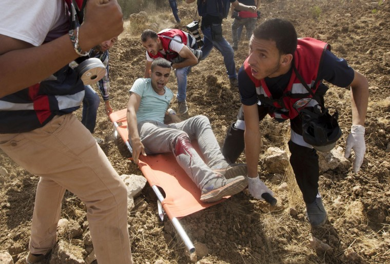 Paramedics help a wounded wounded Palestinian during clashes with Israeli troops near Ramallah, West Bank, Tuesday, Sept. 29, 2015. Palestinian demonstrators clashed with Israeli troops across the West Bank on Tuesday as tensions remained high following days of violence at Jerusalem's most sensitive holy site, revered by Jews as the Temple Mount and by Muslims as the Noble Sanctuary. (AP Photo/Majdi Mohammed)