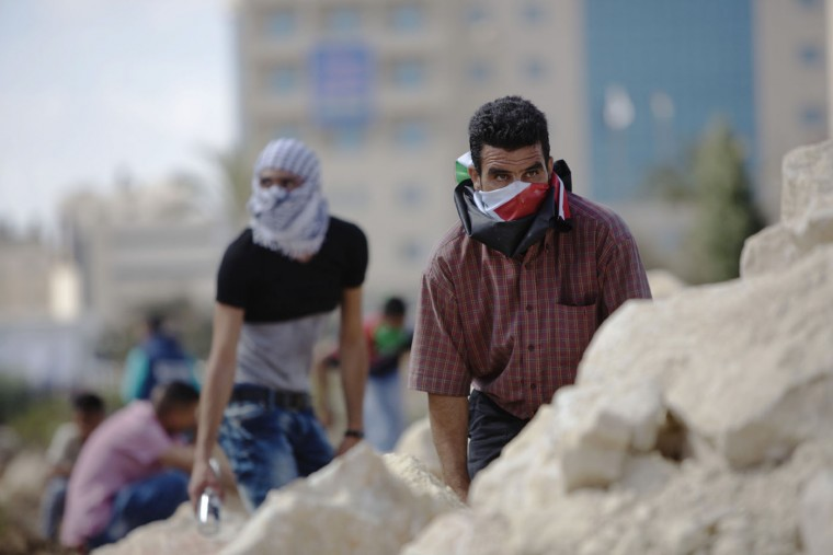 Palestinian demonstrators take cover during clashes with Israeli troops near Ramallah, West Bank, Tuesday, Sept. 29, 2015. Palestinian demonstrators clashed with Israeli troops across the West Bank on Tuesday as tensions remained high following days of violence at Jerusalem's most sensitive holy site, revered by Jews as the Temple Mount and by Muslims as the Noble Sanctuary. (AP Photo/Majdi Mohammed)