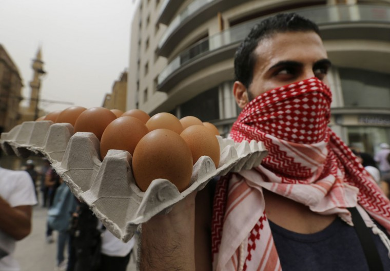 A Lebanese anti-government protester holds eggs, to throw them on the convoys of Lebanese politicians arriving at the parliament building, during a protest against the on-going trash crisis and government corruption, in downtown Beirut, Lebanon, Wednesday, Sept. 9, 2015. Lebanon's prime minister says he hopes that political talks between senior politicians will help end government paralysis that has sparked angry street protests. (AP Photo/Hassan Ammar)