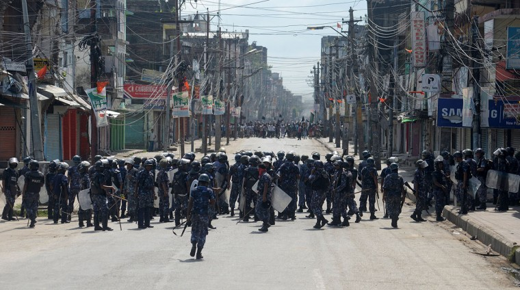 Nepalese policemen face ethnic Madhesis during a protest against the country's new constitution in Birgunj, Nepal, Sunday, Sept. 20, 2015. The new constitution replaces an interim one that was supposed to be in effect for only a couple of years but has governed the nation since 2007. Police said clashes between officers and protesters on Sunday left one demonstrator dead near Birgunj town in southern Nepal. (AP Photo/ Manish Paudel)