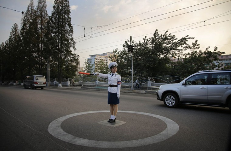 A North Korean traffic police woman directs vehicles at an intersection, Tuesday, Sept. 15, 2015, in Pyongyang, North Korea, as residents commute at the end of the work day. (AP Photo/Wong Maye-E)