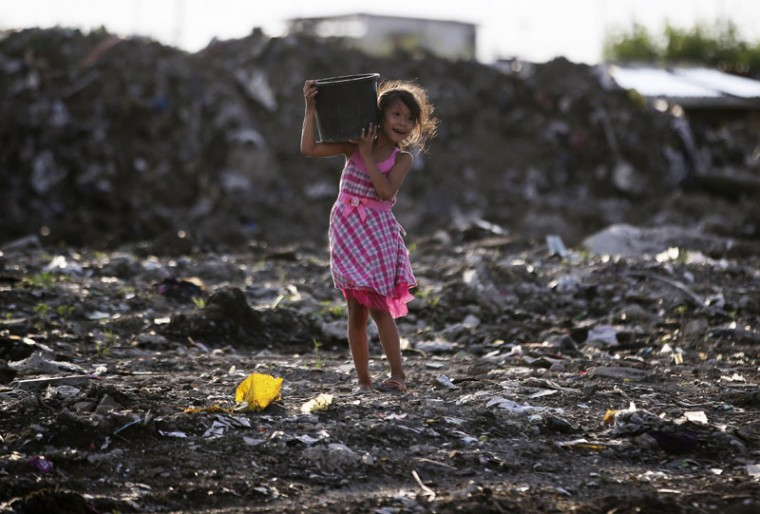 A Filipino girl carries a bucket filled with rocks which she gathered near her home in suburban Paranaque, south of Manila, Philippines, Sunday, Sept. 6, 2015. The girl said the rocks would be used to build barriers to prevent floodwaters from entering her family home. (AP Photo/Aaron Favila)