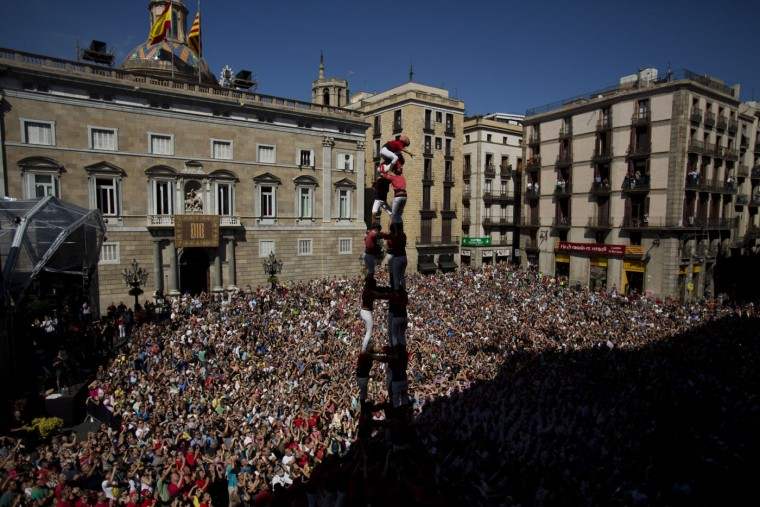 "Members of the Castellers Joves Xiquets de Valls form a human tower or ""Castellers"" during the Saint Merce celebrations in San Jaime square in Barcelona, Spain, Sunday, Sept. 20, 2015. The tradition of building human towers or ""castells"" dates back to the 18th century and takes place during festivals in Catalonia, where ""colles"" or teams compete to build the tallest and most complicated towers. A ""castell"" is considered completely successful when it is loaded and unloaded without falling apart. In 2010 ""castells"" were declared by UNESCO one of the Masterpieces of the Oral and Intangible Heritage of Humanity. (AP Photo/Emilio Morenatti)"