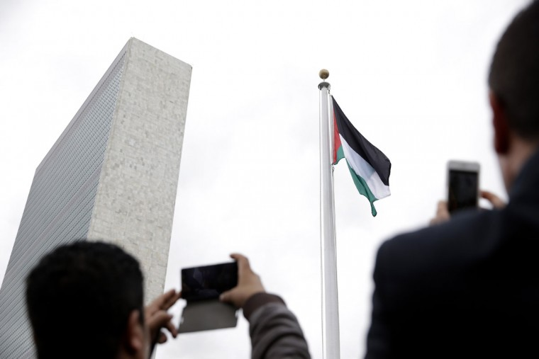 People photograph the State of Palestine flag as it flies for the first time at U.N. headquarters, Wednesday, Sept. 30, 2015. (AP Photo/Seth Wenig)