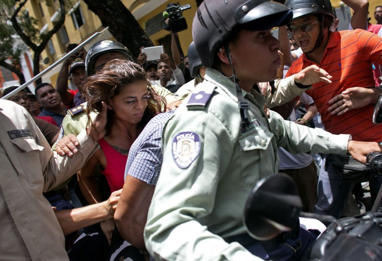 A woman is detained by national police during clashes between supporters of jailed opposition leader Leopoldo Lopez and government loyalists outside the courthouse in Caracas, Venezuela, Thursday, Sept. 10, 2015. Supporters of a high-profile jailed Venezuelan opposition leader clashed with government loyalists Thursday outside a Caracas courthouse in anticipation of an impending verdict. (AP Photo/Ariana Cubillos)