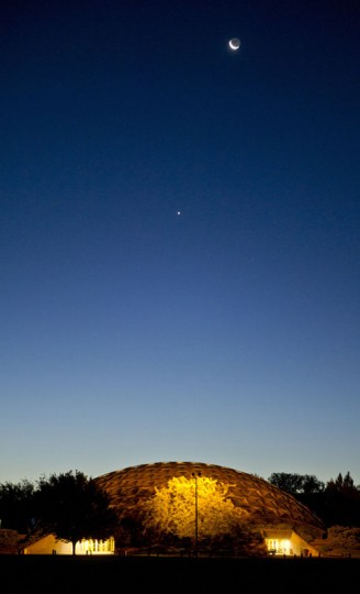 The waning crescent moon, rounded out with earthshine on the dark side and followed by Venus, rises above the Walla Walla Community College's Dietrich Dome before dawn early Wednesday morning, Sept. 9, 2015, in Walla Walla, Wash. (Greg Lehman/Walla Walla Union-Bulletin via AP)