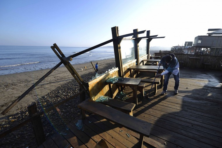 A man sweeps broken glasses at a beach-side bar damaged by an earthquake-triggered tsunami in Concon, Chile, Thursday, Sept. 17, 2015. Several coastal towns were flooded from small tsunami waves set off by late Wednesday's magnitude-8.3 earthquake, which shook the Earth so strongly that rumbles were felt across South America. (AP Photo/Matias Delacroix)