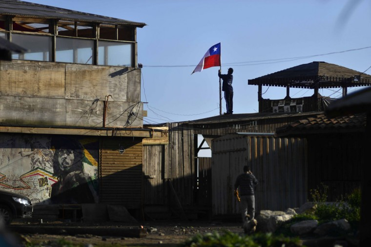 A man secures a Chilean flag on a roof after an earthquake-triggered tsunami damaged homes and businesses in Concon, Chile, Thursday, Sept. 17, 2015. Several coastal towns were flooded from small tsunami waves set off by late Wednesday's magnitude-8.3 earthquake, which shook the Earth so strongly that rumbles were felt across South America. (AP Photo/Matias Delacroix)
