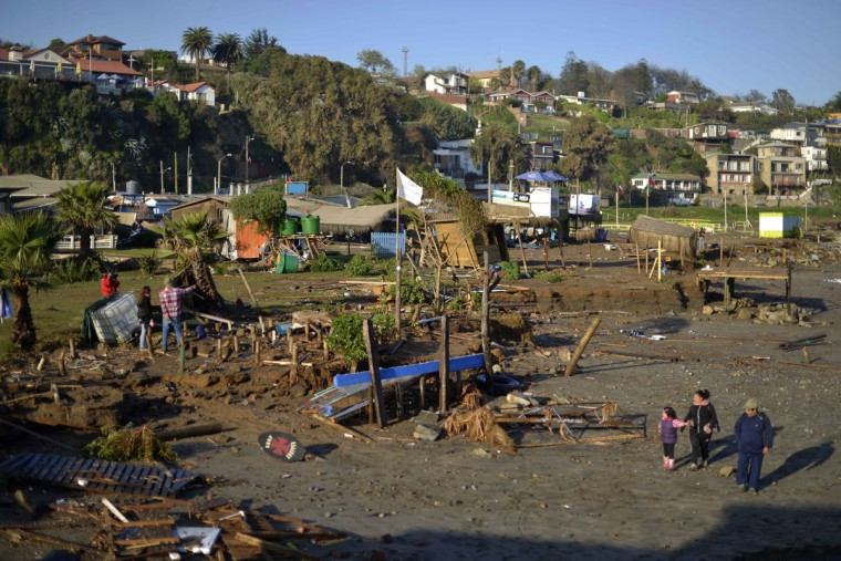 People walk past destroyed surfing schools on the beach after an earthquake-triggered tsunami in Concon, Chile, Thursday, Sept. 17, 2015. Several coastal towns were flooded from small tsunami waves set off by late Wednesday's magnitude-8.3 earthquake, which shook the Earth so strongly that rumbles were felt across South America. (AP Photo/Matias Delacroix)