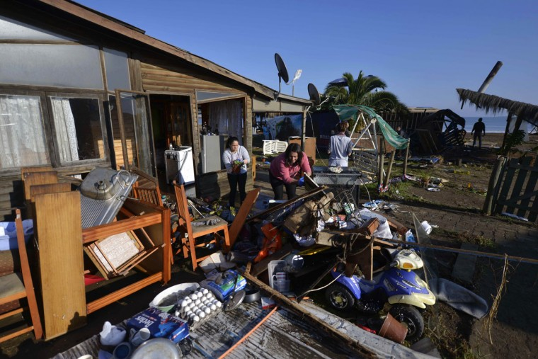 Women dry their belonging outside their home after an earthquake-triggered tsunami flooded their home in Concon, Chile, Thursday, Sept. 17, 2015. Several coastal towns were flooded from small tsunami waves set off by late Wednesday's magnitude-8.3 earthquake, which shook the Earth so strongly that rumbles were felt across South America. (AP Photo/Matias Delacroix)