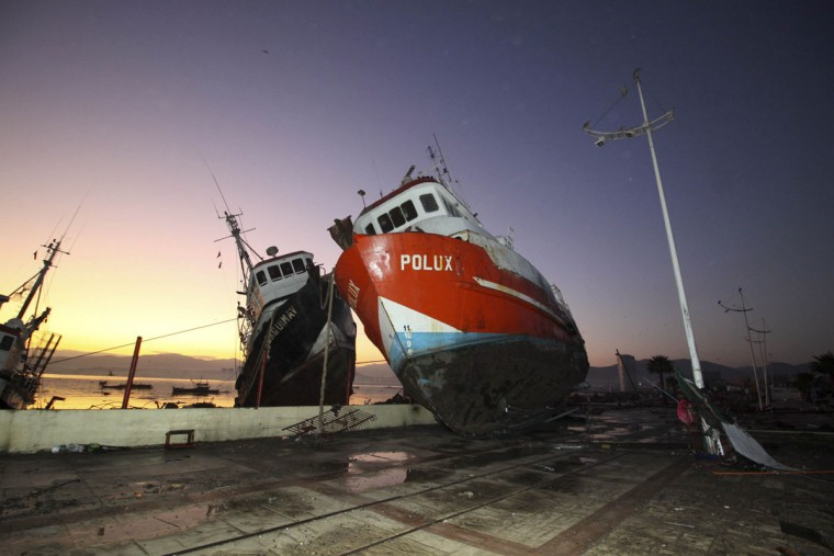 A boat stands on a dock after it was lifted by an earthquake-triggered tsunami in Coquimbo, Chile, Thursday, Sept. 17, 2015. Several coastal towns were flooded from small tsunami waves set off by late Wednesday's magnitude-8.3 earthquake, which shook the Earth so strongly that rumbles were felt across South America. (Agencia Uno/Hernan Contreras via AP)