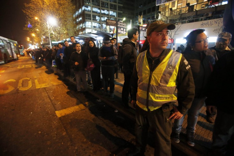 A police officer stands in the street to direct traffic as people stand in a line for public transportation after an earthquake in Santiago, Chile, Wednesday, Sept. 16, 2015. A powerful magnitude-8.3 earthquake hit off Chile's northern coast Wednesday night, causing buildings to sway in Santiago and other cities and sending people running into the streets. (AP Photo/Luis Hidalgo)
