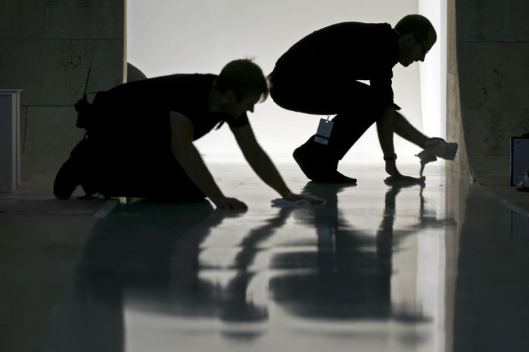 Workers clean the runway before the Victoria Beckham Spring 2016 collection is modeled during Fashion Week, in New York, Sunday, Sept. 13, 2015. (AP Photo/Richard Drew)