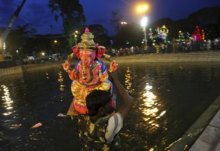 A volunteer carries an idol of elephant-headed Hindu god Ganesha for immersion in a pond during Ganesh Chaturthi festival celebrations in Bangalore, India, Thursday, Sept. 17, 2015. The festival marks the birthday of Lord Ganesha who is widely worshiped by Hindus as the god of wisdom, prosperity and good fortune. (AP Photo/Aijaz Rahi)
