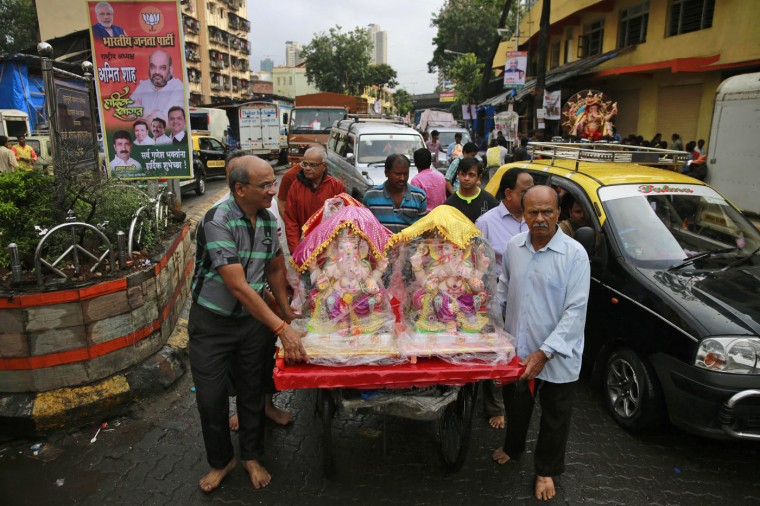 Devotees carry idols of elephant-headed Hindu god Ganesha on a handcart during Ganesha Chaturthi festival in Mumbai, India, Thursday, Sept. 17, 2015. Ganesh Chaturthi is celebrated as the birthday of Lord Ganesha and the 10-day festival ends with immersion of the idols in water bodies. (AP Photo/Rafiq Maqbool)