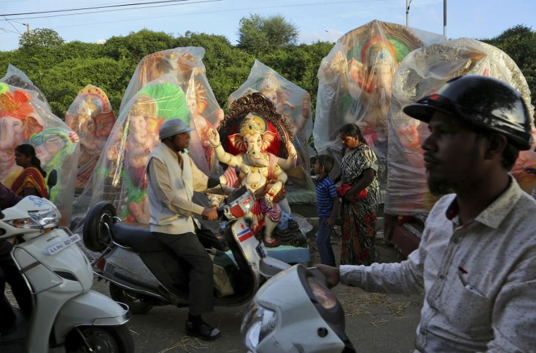 Indian commuters pass by a row of idols of elephant headed Hindu god Ganesha displayed for sale ahead of Ganesh Chaturthi festival in Bangalore, India, Wednesday, Sept.16, 2015. After worshipping the idols in their homes or specially set up worship venues, devotees immerse them in water bodies at the end of the festival. (AP Photo/Aijaz Rahi)