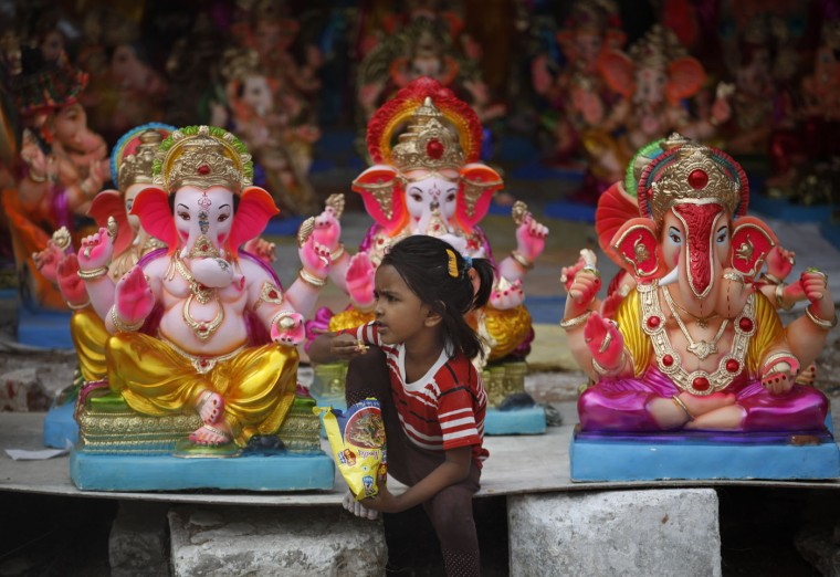 An Indian child eats snacks as she sits in front of idols of elephant-headed Hindu god Ganesha displayed for sale ahead of Ganesha Chaturthi festival in Ahmadabad, India, Tuesday, Sept. 15, 2015. The ten day long Ganesh festival begins on Sept. 17. (AP Photo/Ajit Solanki)