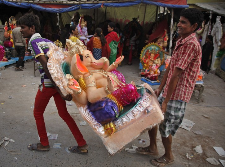 Indians carry an idol of elephant-headed Hindu god Ganesha for sale ahead of Ganesha Chaturthi festival in Ahmadabad, India, Tuesday, Sept. 15, 2015. The ten day long Ganesh festival begins on Sept. 17. (AP Photo/Ajit Solanki)