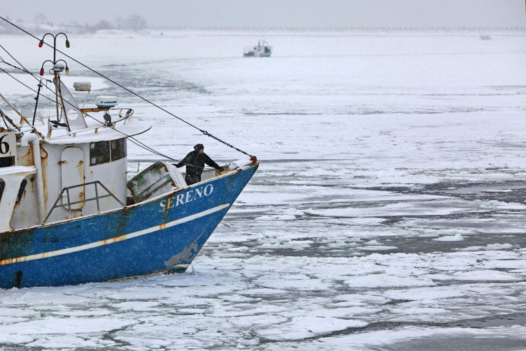 A crew member of the fishing boat Sereno stands on the bow while looking for a docking berth as it arrives into a frozen New Bedford, Mass. harbor. The commercial fishing industry is a year-round business that continues through brutally cold New England winters. (Peter Pereira/The Standard-Times via AP)