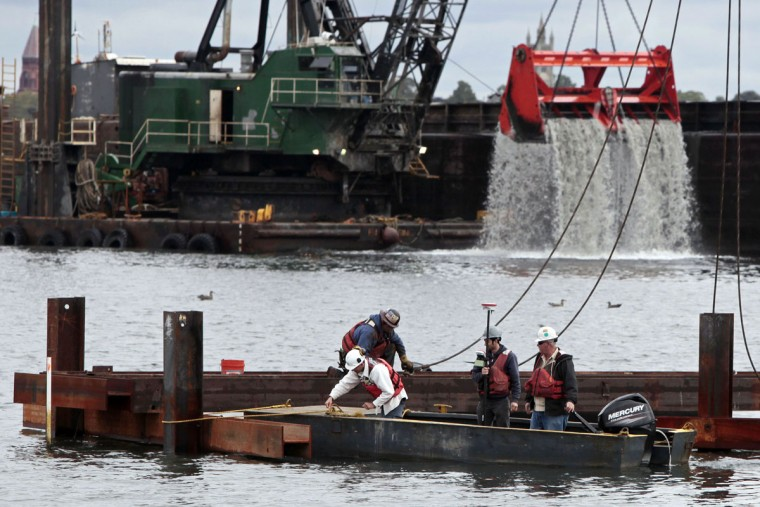 Crews install the first sheet pile walls as work begins on constructing the New Bedford Marine Commerce Terminal in the south end of New Bedford, Mass., as a crane dredges the harbor, background. Costly dredging to remove silt is needed regularly to keep deep-water ports active. In a city known for it's commercial fishing industry, the new terminal would be the first facility in the nation for constructing and deploying offshore wind power projects when completed. (Peter Pereira/The Standard-Times via AP)