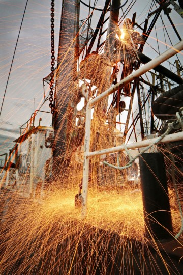 Welder Joe Pinto cuts the rusted supporting A-frame from the structure of the fishing vessel Titan docked in New Bedford, Mass. In its heyday in the mid-1800s, the city was the undisputed hub of the global whaling industry. Whales are no longer part of the equation, and commercial fishing isn't as lucrative as it was then. But it remains a viable industry and vital to New Bedford and the surrounding region. (Peter Pereira/The Standard-Times via AP)
