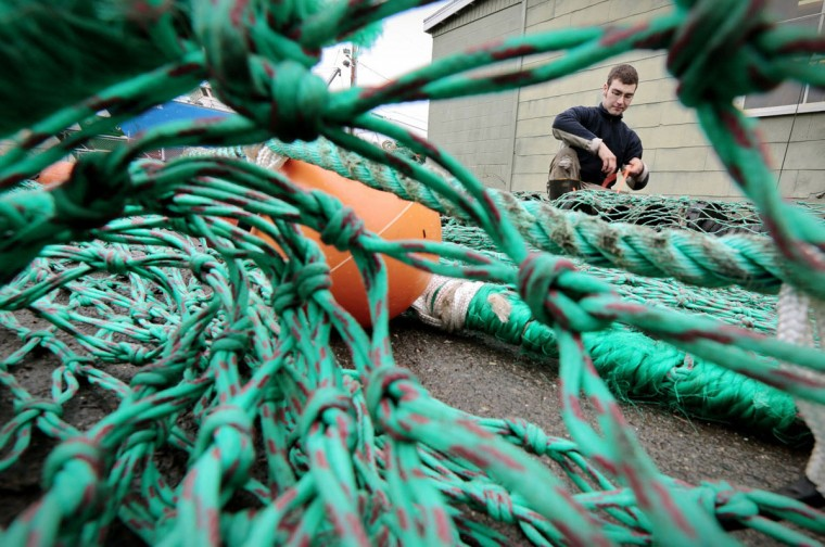 Karl Hotys repairs a groundfishing net at Reidar's Manufacturing in Fairhaven, Mass. Groundfish such as cod, flounder, halibut, and sole live on or near the bottom of the ocean. (Peter Pereira/The Standard-Times via AP)