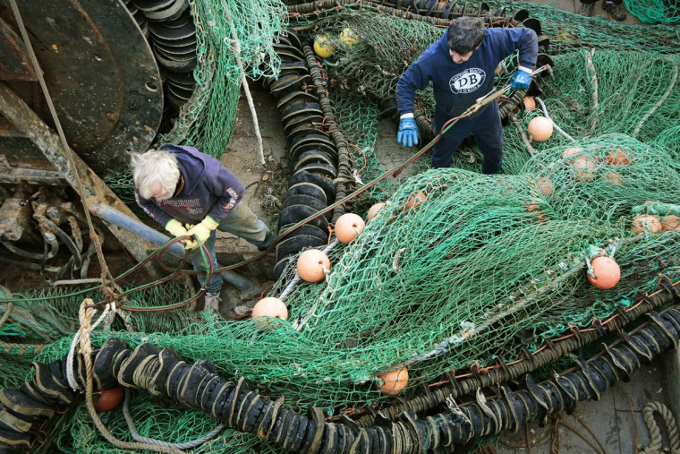 Fishermen repair the nets aboard the fishing vessel Humbak docked at State Pier in New Bedford, Mass. In the mid-1800s, the city was the undisputed hub of the global whaling industry, when it existed. The commercial fishing industry remains viable, but not as lucrative as in earlier times. (Peter Pereira/The Standard-Times via AP)