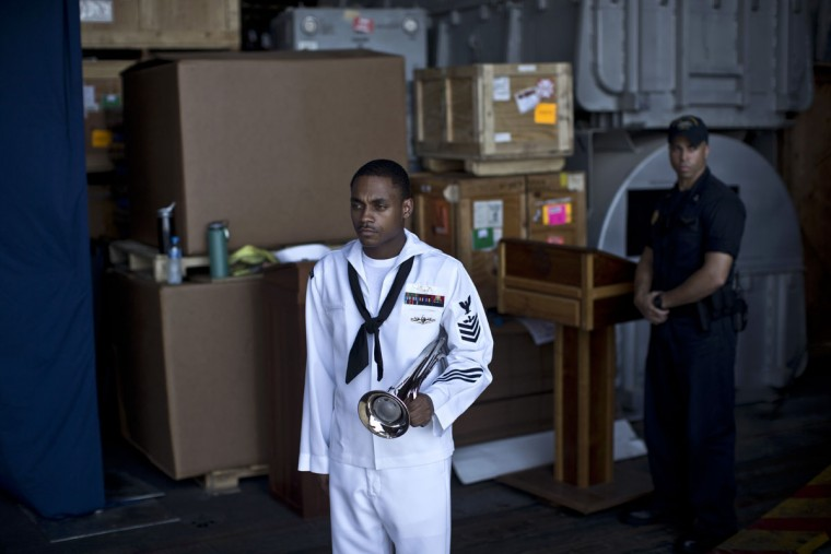 A U.S. Navy sailor carries a trumpet before a Sept. 11 remembrance ceremony on board the USS Theodore Roosevelt aircraft carrier deployed in the Persian Gulf in support of Operation Inherent Resolve, the military operation against Islamic State extremists in Syria and Iraq. (AP Photo/Marko Drobnjakovic)