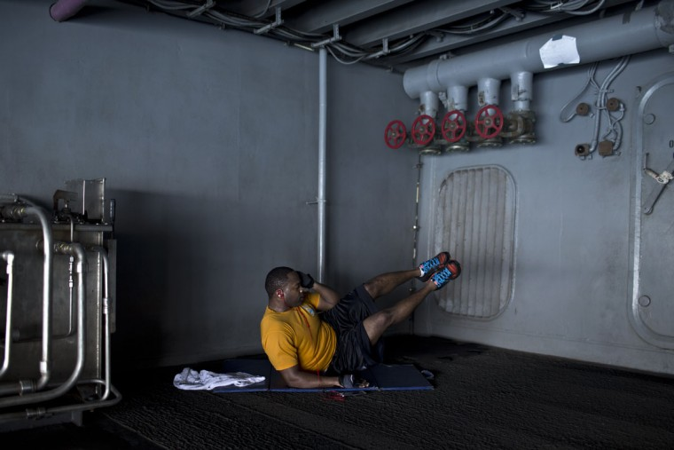 A U.S. Navy sailor works out in an area designated for exercise on board the USS Theodore Roosevelt aircraft carrier currently deployed in the Persian Gulf, supporting Operation Inherent Resolve, the military operation against Islamic State extremists in Syria and Iraq. Below deck is a complex set of passageways and tunnels, hangars and sailorsí quarters, gyms and mess halls, engine rooms and offices. Painted murals bear fighter squadron insignia, U.S. flags, the cartoon figure Popeye and other patriotic imagery.(AP Photo/Marko Drobnjakovic)