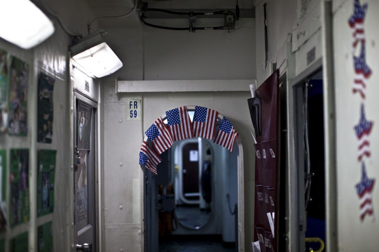 U.S. flags decorate a door frame on board USS Theodore Roosevelt aircraft carrier currently deployed in the Persian Gulf, supporting Operation Inherent Resolve, the military operation against Islamic State extremists in Syria and Iraq. (AP Photo/Marko Drobnjakovic)