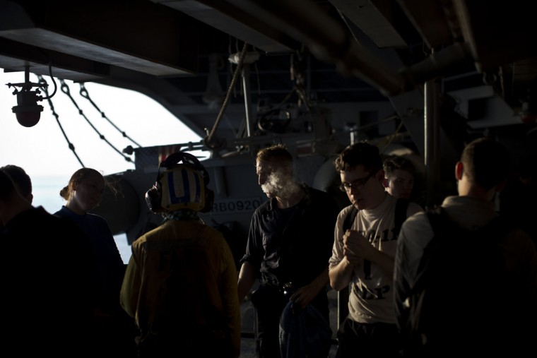 U.S. Navy personnel smoke cigarettes on board the USS Theodore Roosevelt aircraft carrier currently deployed in the Persian Gulf, supporting Operation Inherent Resolve, the military operation against Islamic State extremists in Syria and Iraq. (AP Photo/Marko Drobnjakovic)