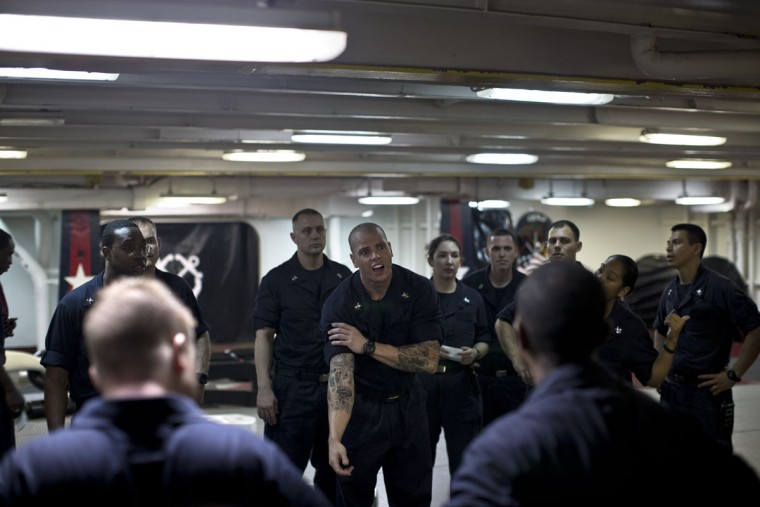 A group of U.S. Navy Petty Officers First Class to be promoted into higher rank discuss the promotion ceremony protocol on board the USS Theodore Roosevelt aircraft carrier currently deployed in the Persian Gulf, supporting Operation Inherent Resolve, the military operation against Islamic State extremists in Syria and Iraq. (AP Photo/Marko Drobnjakovic)