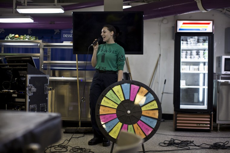 A U.S. Navy sailor participates in Karaoke night inside one of the USS Theodore Roosevelt aircraft carrier mess halls during deployment in the Persian Gulf. The carrier, currently running airstrikes against Islamic State targets in Syria and Iraq, is home and base to approximately five thousand personnel while on deployment, and the ship's mess halls serve up to eighteen thousand meals to sailors on a daily basis. (AP Photo/Marko Drobnjakovic)