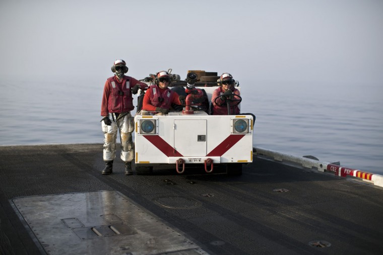 A crash and salvage team, wearing red shirts, stand ready as they observe flight operations on the deck of the USS Theodore Roosevelt aircraft carrier. Pilots onboard have flown missions into both Iraq and Syria, part of the over 6,800 airstrikes carried out since August 2014. Some 20 percent of all coalition strikes come from aircraft launched from the nuclear-powered Roosevelt.(AP Photo/Marko Drobnjakovic)