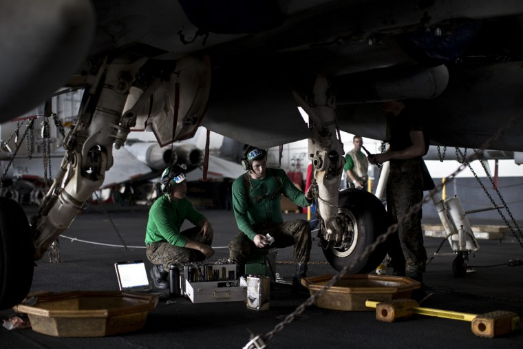 Aircraft mechanics, wearing green jerseys, perform maintenance on the landing gear of a U.S. fighter jet inside the hangar on board the USS Theodore Roosevelt currently deployed in the Persian Gulf, supporting Operation Inherent Resolve, the military operation against Islamic State extremists in Syria and Iraq. (AP Photo/Marko Drobnjakovic)
