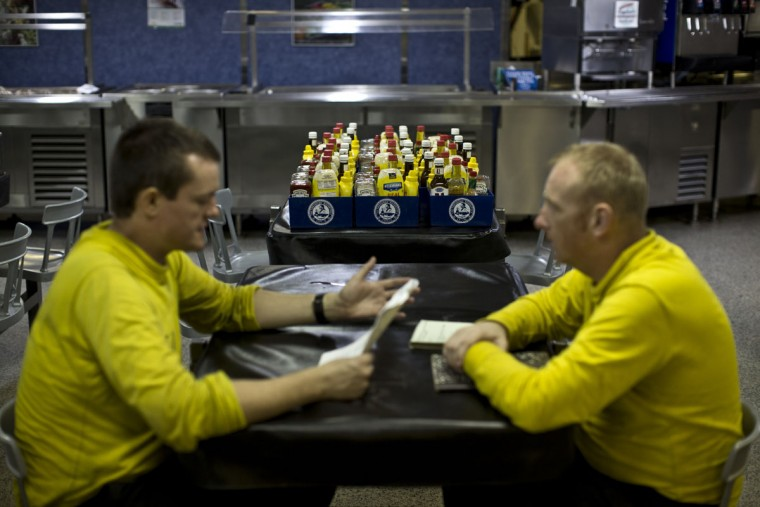 U.S. Navy sailors have a conversation inside one of the USS Theodore Roosevelt aircraft carrier mess halls. The carrier, currently running airstrikes against Islamic State targets in Syria and Iraq, is home and base to approximately five thousand personnel while on deployment, and the ship's mess halls serve up to eighteen thousand meals to sailors on a daily basis. (AP Photo/Marko Drobnjakovic)