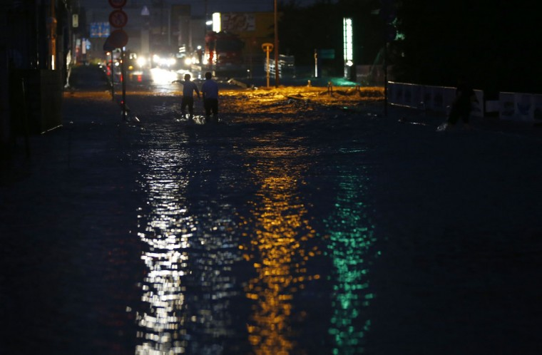 People walk through a flooded street in Joso, Ibaraki prefecture, north of Tokyo, Thursday, Sept. 10, 2015. Raging floodwaters broke through a flood berm Thursday and swamped the city north of Tokyo, washing away houses, forcing dozens of people to rooftops to await helicopter rescues. (AP Photo/Shizuo Kambayashi)